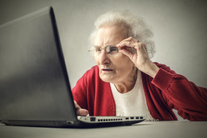 Older woman peering at computer